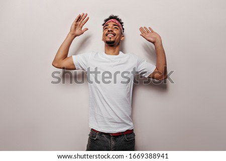 Joyful guy in white T-shirt and black jeans is dancing. Portrait of charming man in tee and pants smiling on isolated background Royalty-Free Stock Photo #1669388941