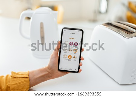 Controlling smart kitchen appliance using mobile phone at home, close-up on mobile screen. Concept of a smart home devices #1669393555
