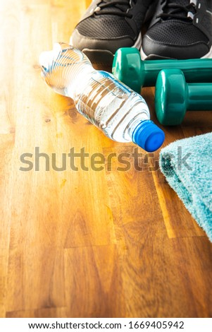 Fitness concept. Black sports shoes, dumbbell and bottle of water on wooden floor. #1669405942