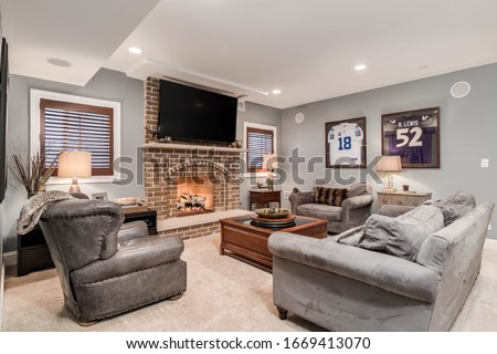 ELMHURST, IL, USA - JANUARY 30, 2020: A man cave, living room with a television mounted above a lit fireplace and football jerseys mounted on the wall. #1669413070
