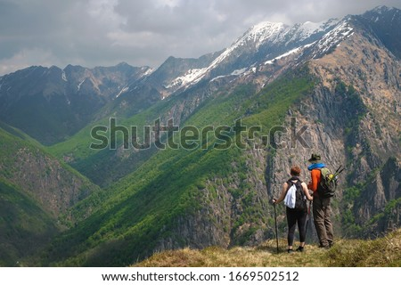 Couple of young hikers, admire the stunning  panorama of the wild  Val Grande National Park from the top of the mountain, Europe, Piedmont Italy. #1669502512