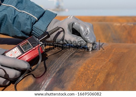 Inspector is measuring thickness of the pipe material from near to weld with a portable ultrasonic wall thickness measurement gauge. It is a method of performing non destructive measurement (gauging). Royalty-Free Stock Photo #1669506082