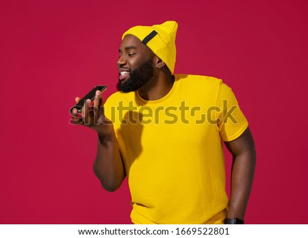 Cheerful man uses the phone, leaves a voice message on red background Royalty-Free Stock Photo #1669522801