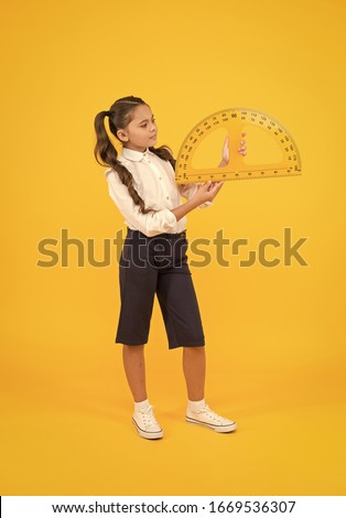 Setting square with protractor. Little girl using triangle to measure angles in degrees on yellow background. Small child holding school protractor for geometry lesson. Learning to use protractor.