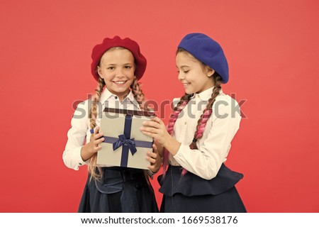 Surprise for both. Friendship concept. Birthday gift present. Shopping and holidays. Girl giving gift box to friend. Girls friends celebrate holiday. Children with wrapped gift. Open gift box.