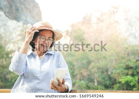Asian senior woman Holding a smartphone, taking a picture and playing social media, she enjoys her retirement life. Elderly community concept. copy space