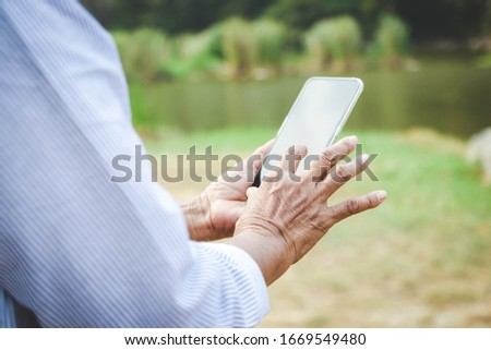 Asian senior woman Holding a smartphone, taking a picture and playing social media, she enjoys her retirement life. Elderly community concept.