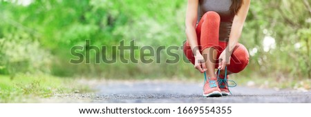 Exercise and sport running shoes runner woman tying laces getting ready for summer run in forest park panoramic banner header crop. Jogging girl exercise motivation heatlhy fit living. #1669554355