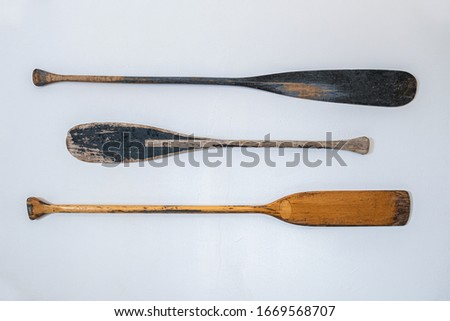 Vintage wooden boat oars hanging on a white plastered wall Royalty-Free Stock Photo #1669568707