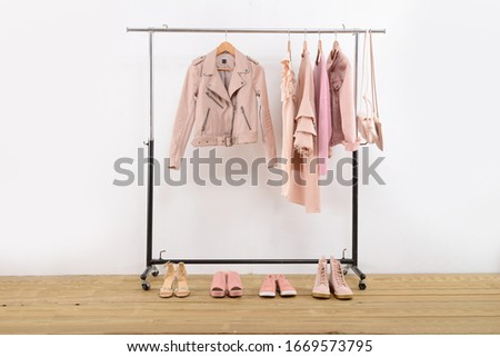Rack with stylish jacket with sundress, shirts, and leather handbag with four shoes on wooden background    #1669573795