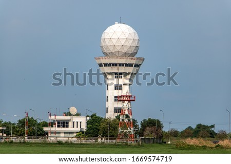 Aeronautical meteorological observations station tower with spherical radar antenna. Control tower with weather radar on airport, on blue sky background. Royalty-Free Stock Photo #1669574719