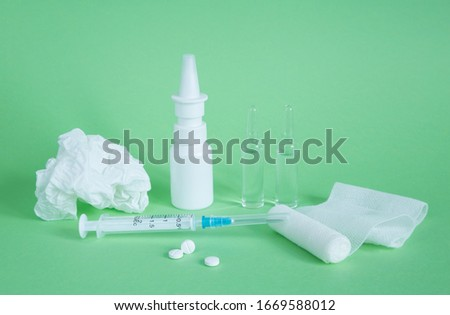 Medical equipment for the treatment of diseases. White medical items on a green background. Drops for nose, crumpled paper scarf, syringe, ampoules, bandage and tablets #1669588012