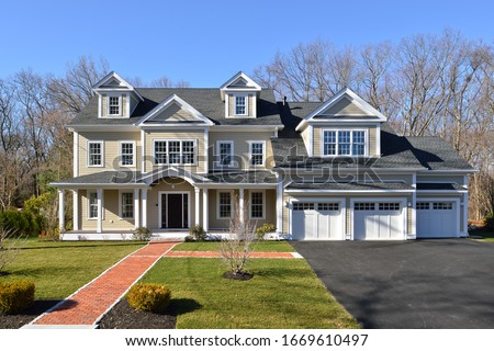 New house, colonial style, frontal view. Brick entrance walkway, paved driveway, landscaped garden. Royalty-Free Stock Photo #1669610497