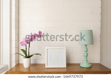 Closeup of purple moth orchid, blank square white picture frame and teal lamp on wooden table against painted brick wall