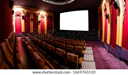 Cinema theater screen in front of seat rows in movie theater showing white screen projected from cinematograph. The cinema theater is decorated in classical style for luxury feeling of movie watching. #1669765510