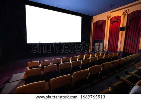 Cinema theater screen in front of seat rows in movie theater showing white screen projected from cinematograph. The cinema theater is decorated in classical style for luxury feeling of movie watching. #1669765513