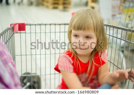 Adorable girl in red sit at shopping cart in supermarket #166980809