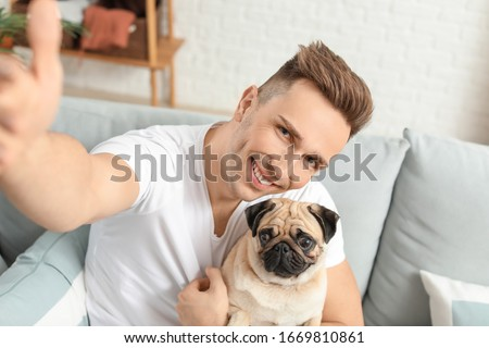 Handsome man taking selfie with cute pug dog at home