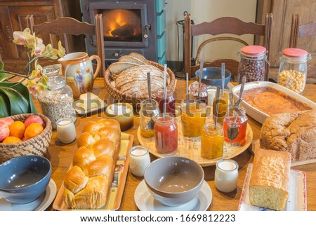 Rustic french breakfast in a old traditional house, with wooden furniture. Served with jam, bread, cake, milk, fruits.