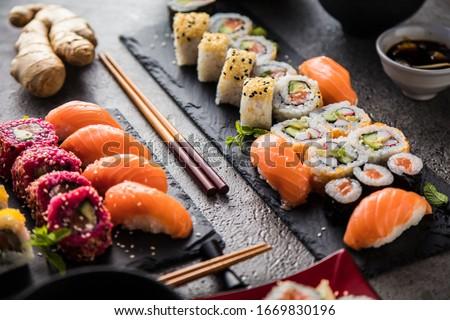 apanese sushi food. Maki ands rolls with tuna, salmon, shrimp, crab and avocado. Top view of assorted sushi. Rainbow sushi roll, uramaki, hosomaki and nigiri #1669830196