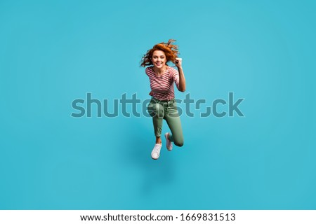 Full length photo of beautiful competitive lady jump high active rush speed marathon winner wear casual red white shirt green trousers footwear isolated blue color background