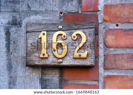 House Number 162 sign. Wooden plate contains brass Number one hundred and sixty-two mounted on a brick wall.