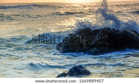 Wave hit the rock at the seaside of beach #1669889407