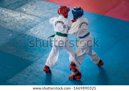 Taekwondo.  Kids in traditional kimano, hard hats and gloves. Sports duel. Text on jacket: Taekwondo is the name for martial art. #1669890325