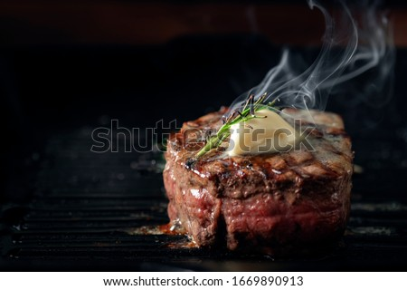 A steaming beef tenderloin steak is grilled in a grill pan with the text copy space. The concept of the recipe , filet Mignon Royalty-Free Stock Photo #1669890913