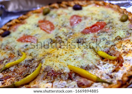 Close up shot of freshly baked pizza.High angle shot of full plate of pizza resting on top of a table inside of a restaurant during the day.Photo of Italian pizza about cheese it stick.Selective focus #1669894885