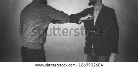 Corona handshake - Two men welcome eachother with their elbows Royalty-Free Stock Photo #1669902604