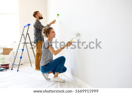 Cheerful couple young  man and woman smiling and  painting white wall with roller during renovation in new apartment Royalty-Free Stock Photo #1669915999