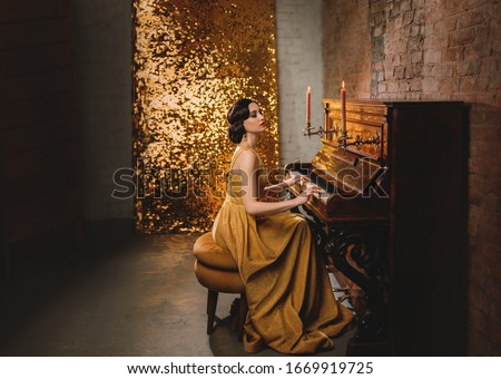 retro romantic elegant woman in golden dress play the piano. backdrop old vintage room brick wall and shine sparkle. Musician with collected bun hairstyle. vogue fashion old style 1920. Carnival party