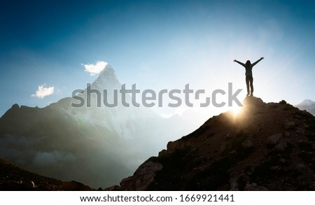 Woman with arms outstretched enjoying the sunrise in the mountains Royalty-Free Stock Photo #1669921441