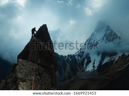Man climber looking for adventure on top of the mountain