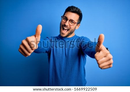 Young handsome man with beard wearing casual sweater and glasses over blue background approving doing positive gesture with hand, thumbs up smiling and happy for success. Winner gesture. #1669922509