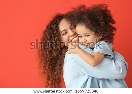 Little African-American girl with her mother on color background