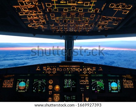 Cockpit view during a early morning flight over the alps Royalty-Free Stock Photo #1669927393