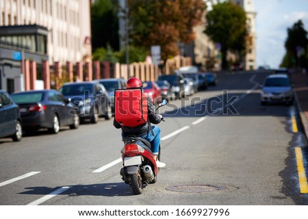 Delivery service from cafes and restaurants, delivery boy on scooter with red backpack driving fast. Courier delivering food on motorbike. Quick deliver food to customers #1669927996