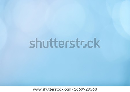 Abstract bokeh sparkle on light blue background