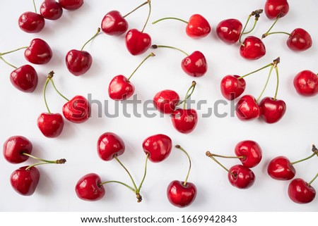Fresh cherries scattered on white. Cherries on a white background. Cherry fruit. Creative fresh cherry pattern background with copy space. Top view. Sprinkled cherry on white background.Isolated fruit #1669942843