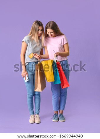 Young women with credit cards and shopping bags on color background #1669944940