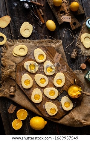 overhead shot of homemade baked egg shaped easter cookies on wooden board on rustic table with yellow eggs, lemon cream. process of baking cookies. easter card #1669957549