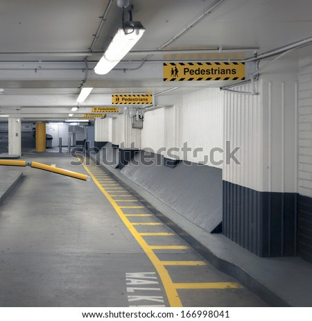 Pedestrian walkway and signage in an undercover parking garage.