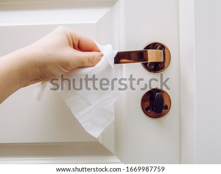 Close up view of woman hand using antibacterial wet wipe for disinfecting home room door link. Royalty-Free Stock Photo #1669987759