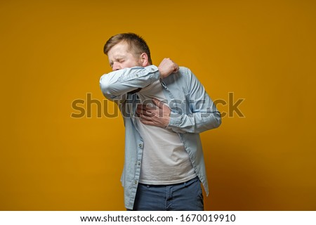 Man coughs in his elbow and holds hand on chest, experiencing pain. Concept of the spread of the virus. Royalty-Free Stock Photo #1670019910