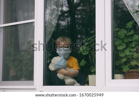 Stay at home quarantine coronavirus pandemic prevention. Sad child and his teddy bear both in protective medical masks sits on windowsill and looks out window. View from street. Prevention epidemic. Royalty-Free Stock Photo #1670025949
