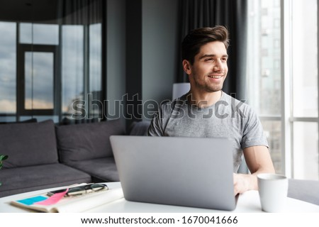 Handsome smiling young bearded man wearing casual clothes using laptop computer while sitting at the table at home #1670041666