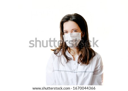 On a white background, a brunette woman in a white medical coat with gray accents and a protective mask on her face close-up in the center of the frame #1670044366