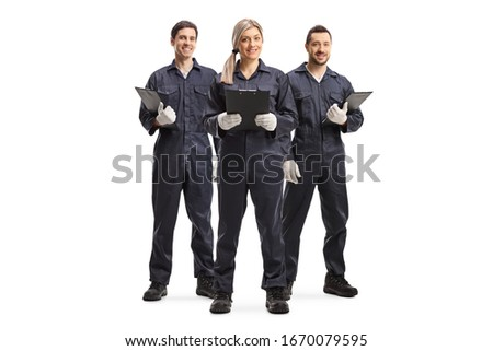 Full length portrait of one female and two male workers in overall uniforms isolated on white background Royalty-Free Stock Photo #1670079595